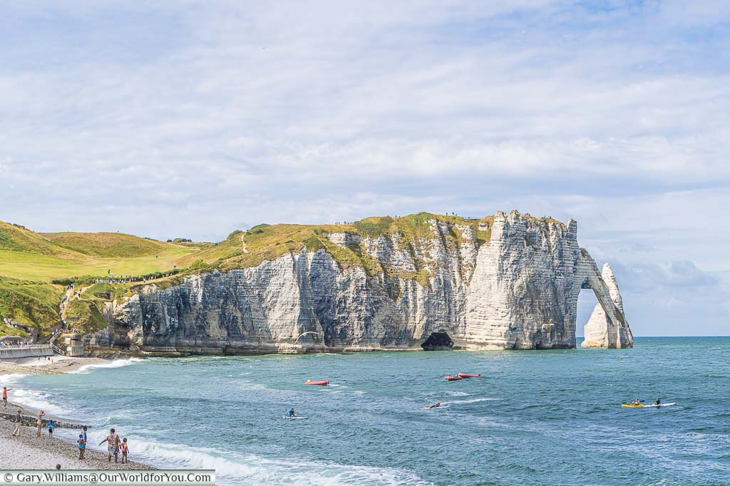 A beach view of Étretat's shoreline, including its white cliffs and legendary arch formation.