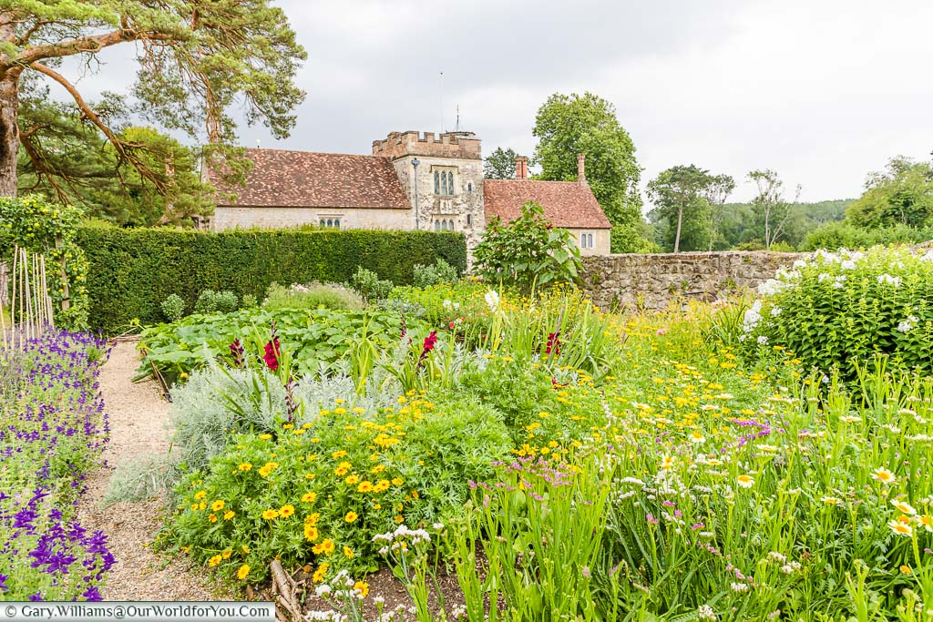 Flowers growing in the walled Cutting Garden, with the entrance to Ightham Mote in the background.