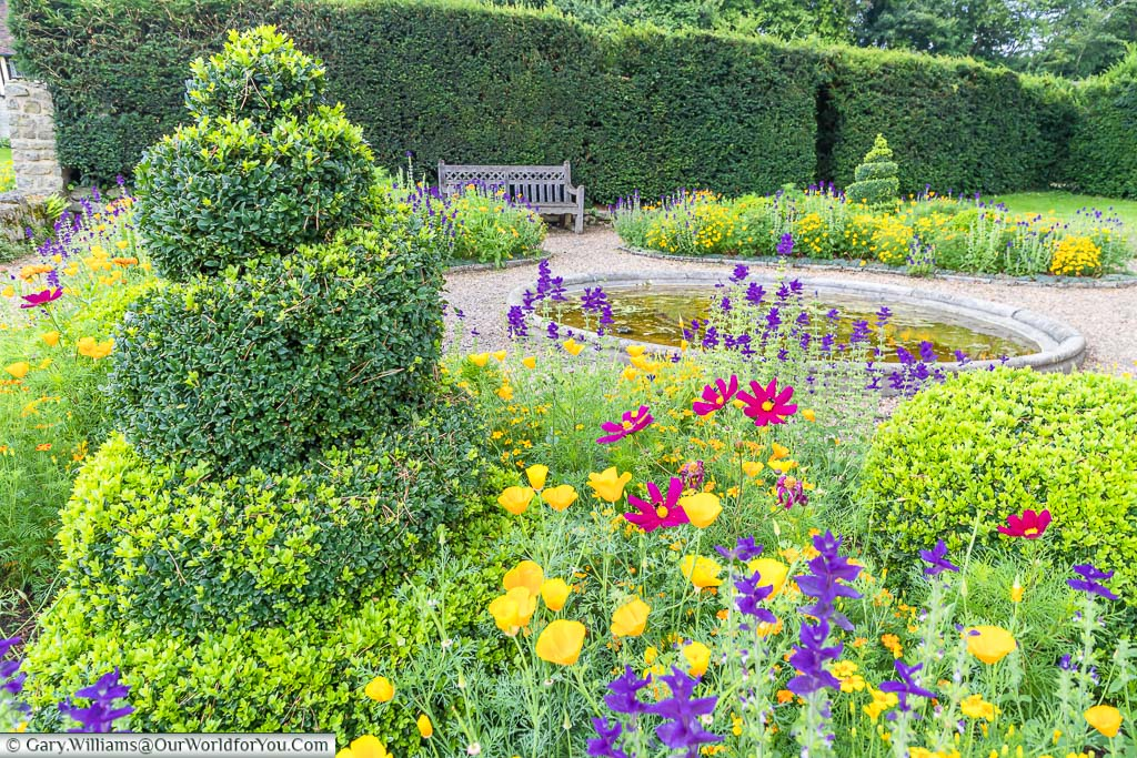 High trimmed hedges line the edges of the Formal Garden of Ightham Mote in Kent