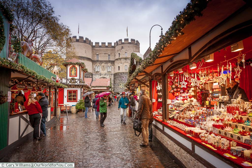 A view of the historic Hahnentorburg gate from within a damp Village of St Nicholas Christmas market in Cologne.