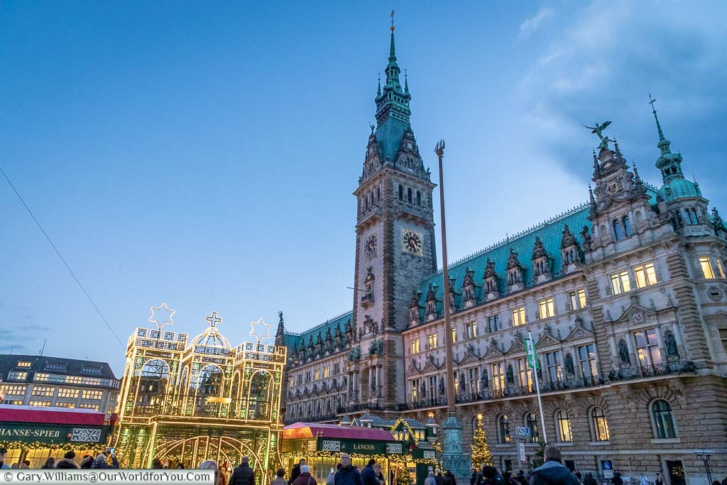 The illuminated golden gateway to the Christmas markets in Hamburg in front of the Green roofed, gothic Rathaus at dusk.