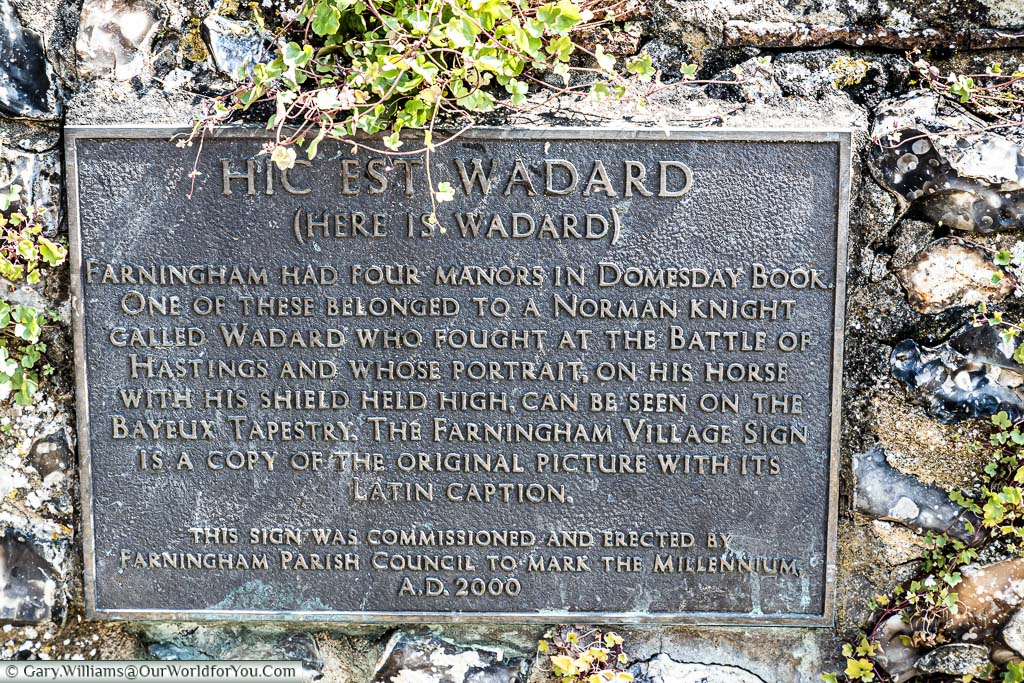 A brass plaque, set in a flint wall, detailing Hic Est Wadard and his place in history at the Battle of Hastings