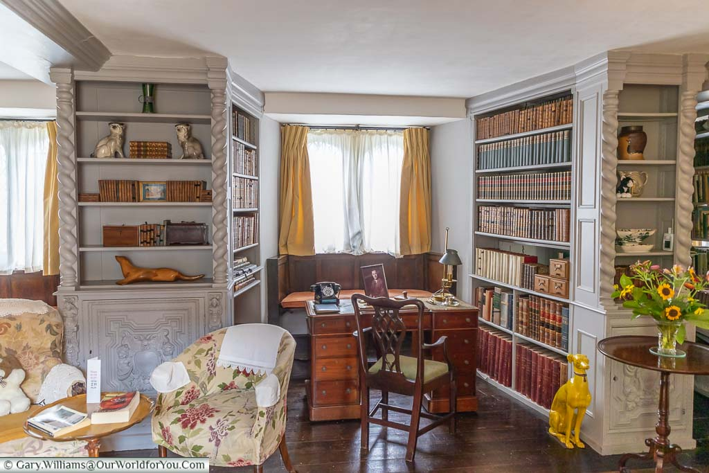 The classic gold & grey interior of the 1950's library at Ightham Mote, featuring a period writing desk.