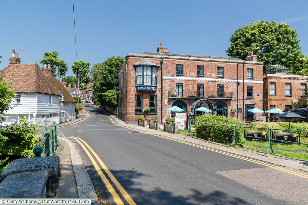 Looking up the high street past the red brick Lion Hotel on the edge of River Darent in Farningham, Kent