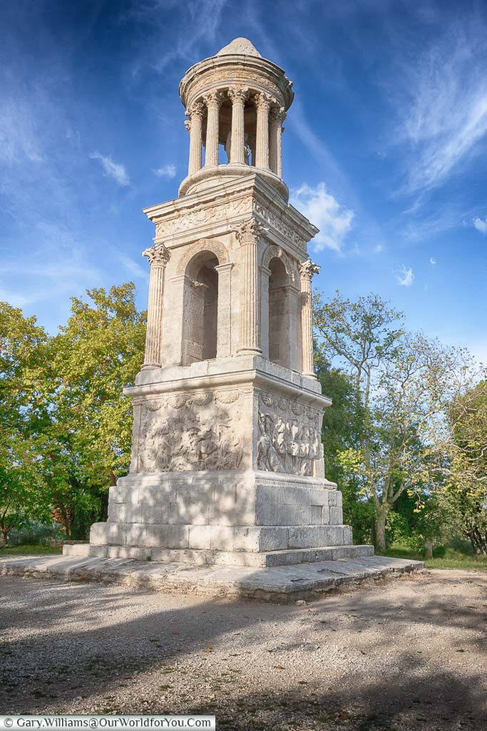 A free standing Roman white stone mausoleum just outside St Remy de Provence set against a blue Sky with wispy white clouds.