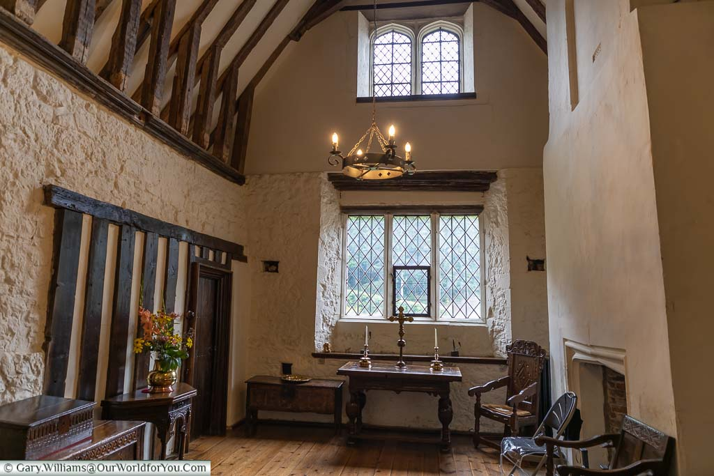The sparse interior of Ightham Mote with its vaulted ceiling and dark wooden furniture.