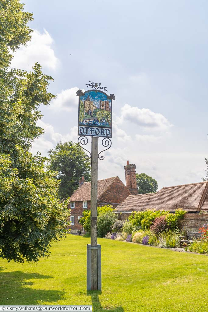 The Otford village sign on a green in front of traditional buildings