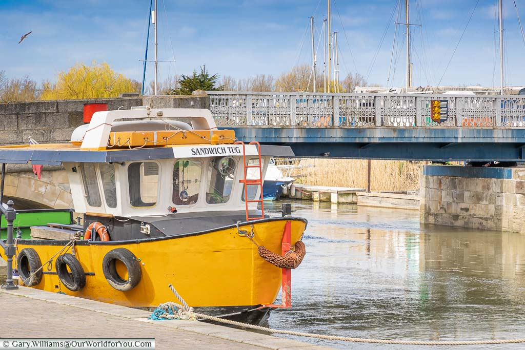 A yellow boat named The Sandwich Tug on the River Stour in Sandwich.