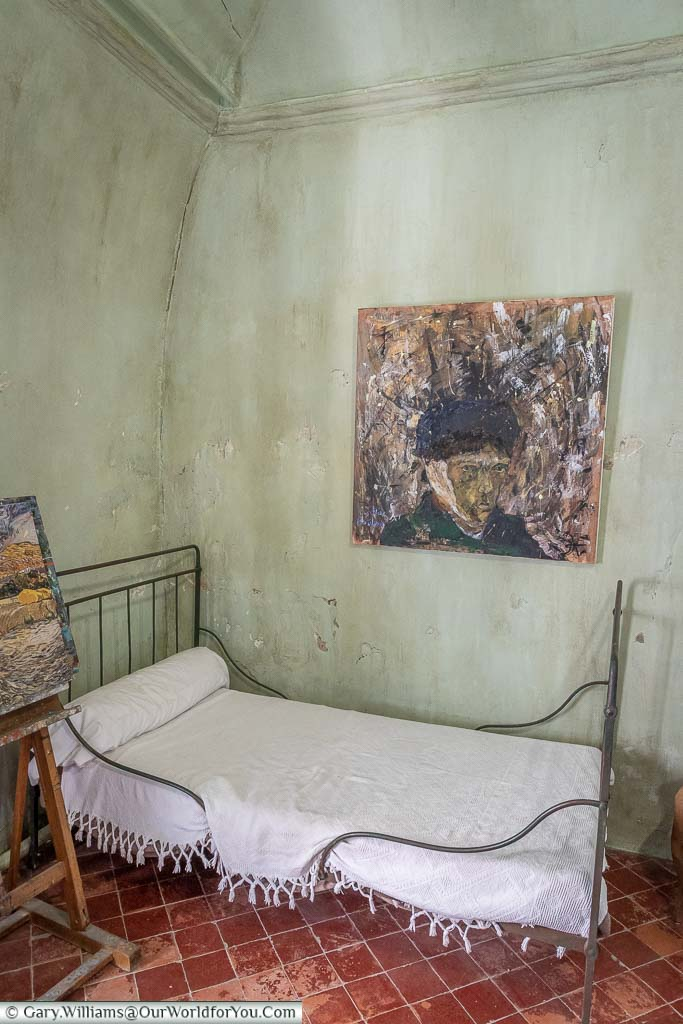 Inside Vincent Van Gough's room in Saint-Paul-de-Mausole. Reproduction of one of his works it's above a small iron framed bed.