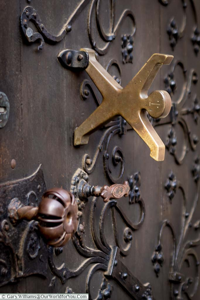 A brass door knocker, on an old wooden door in Düsseldorf, of a figure with outstretched arms as if to perform a cartwheel.