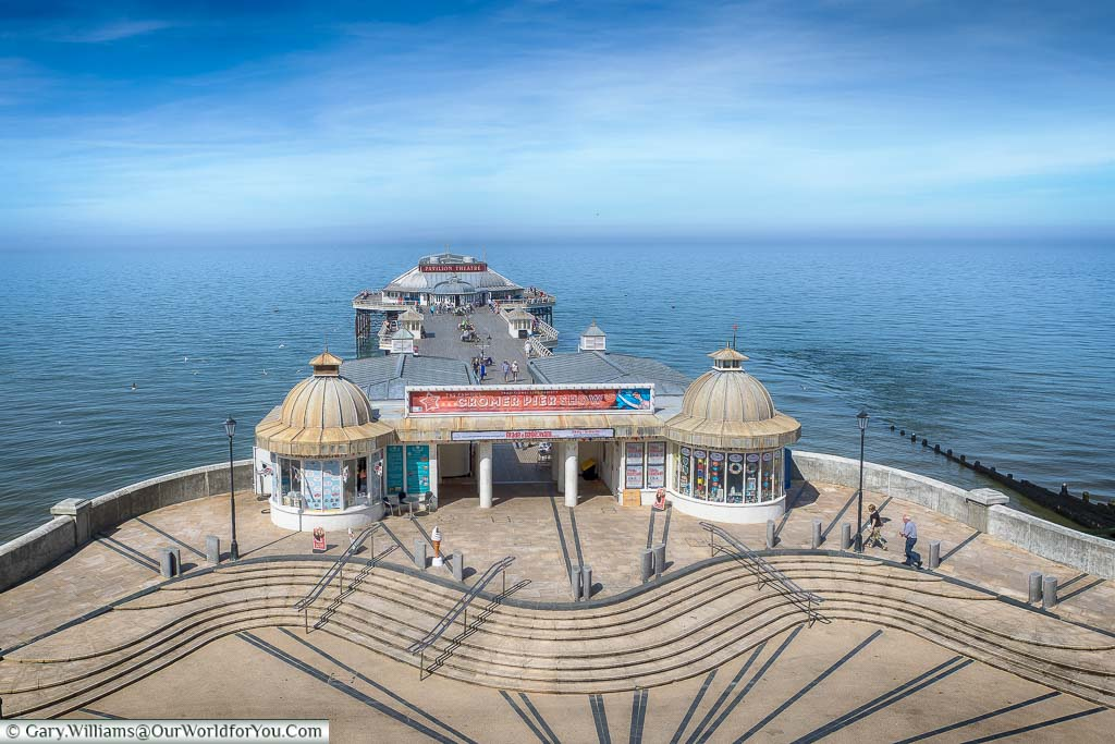 Looking down from the clifftop promenade to the elegant Cromer Pier reaching out to sea on a bright summer's day.