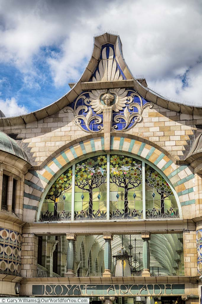 The beautiful art deco glass window and surrounding stonework above the entrance to the Royal Arcade, Norwich