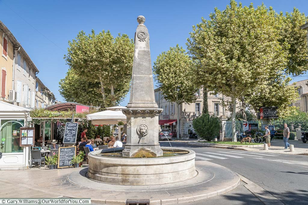 Fountain of the base of an obelisk alongside the periphery road that runs around St Remy de province. Water flows from Lions heads whilst diners eating their lunch at the nearby café.