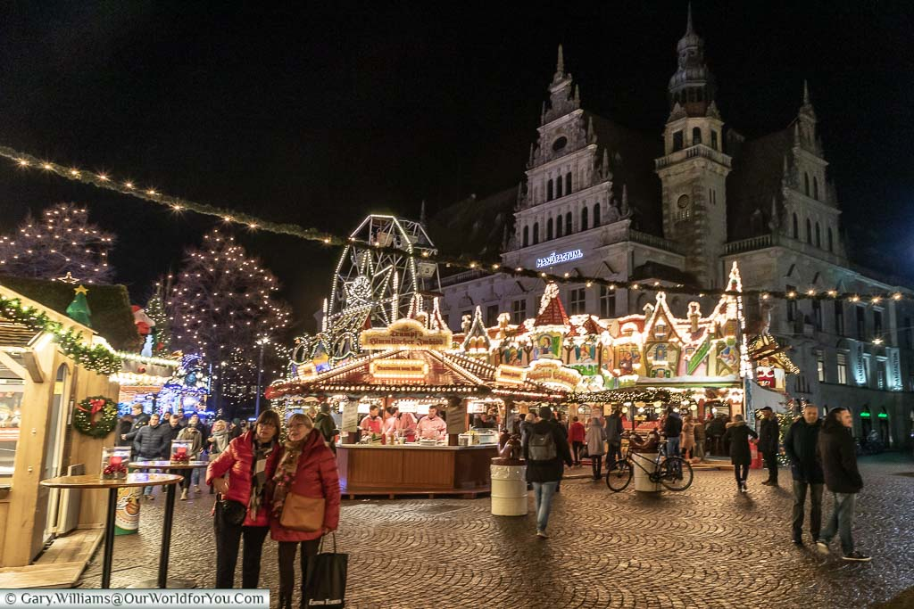 Looking back to a Christmas Market scene in Bremen, in the evening, with a small Ferris wheel and brightly lit huts with people gathering around them.