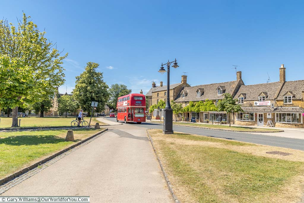 A red Routemaster bus travelling through the village of Broadway in the Cotswolds