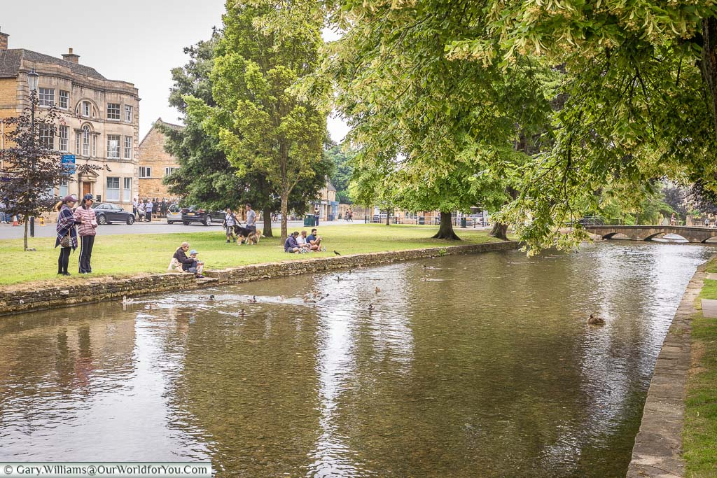 People enjoying the green at Bourton-on-the-water, next to the River Windrush
