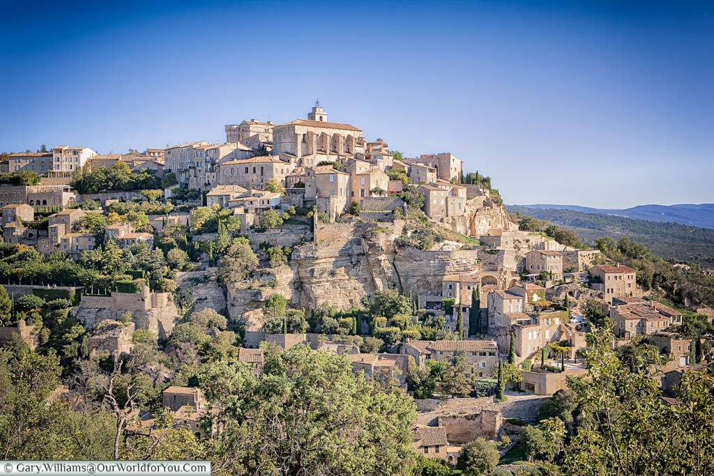 A view of the hillside town of Gordes captured in the glow of the evening sun.