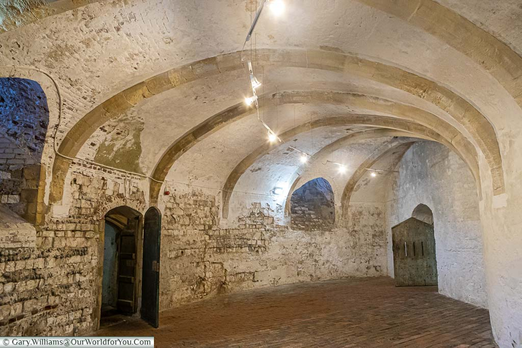 An empty circular stone faulted basement with solid wooden doors in Deal Castle