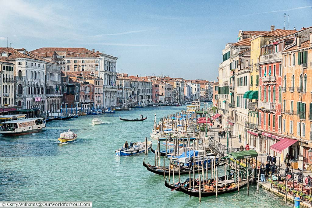 A view from the Rialto Bridge along the busy Grand Canal of Venice, with colourful buildings lining either side