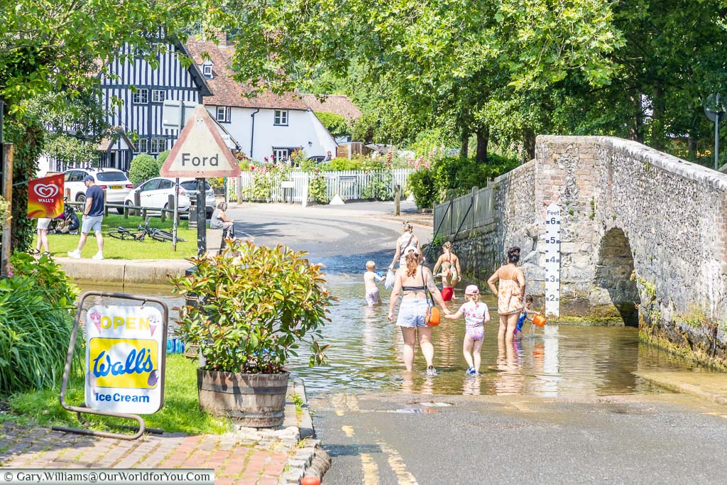A mothers & children wading in the ford, next to the old stone bridge, at Eynsford in Kent