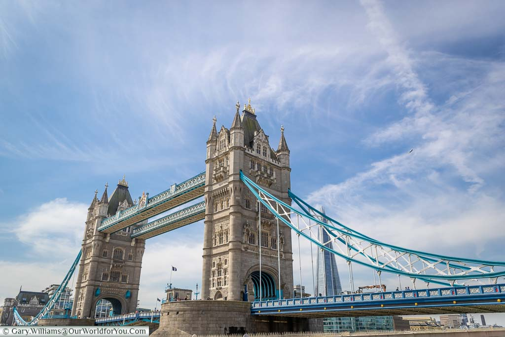 The iconic Tower Bridge, a stone's throw from Tower Hill tube station, on a bright sunny day with the Shard in the background.