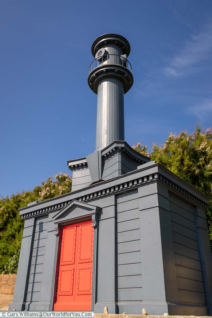 An elaborate blue-grey beach hut with a bright red door in an 18th Century Baroque style.