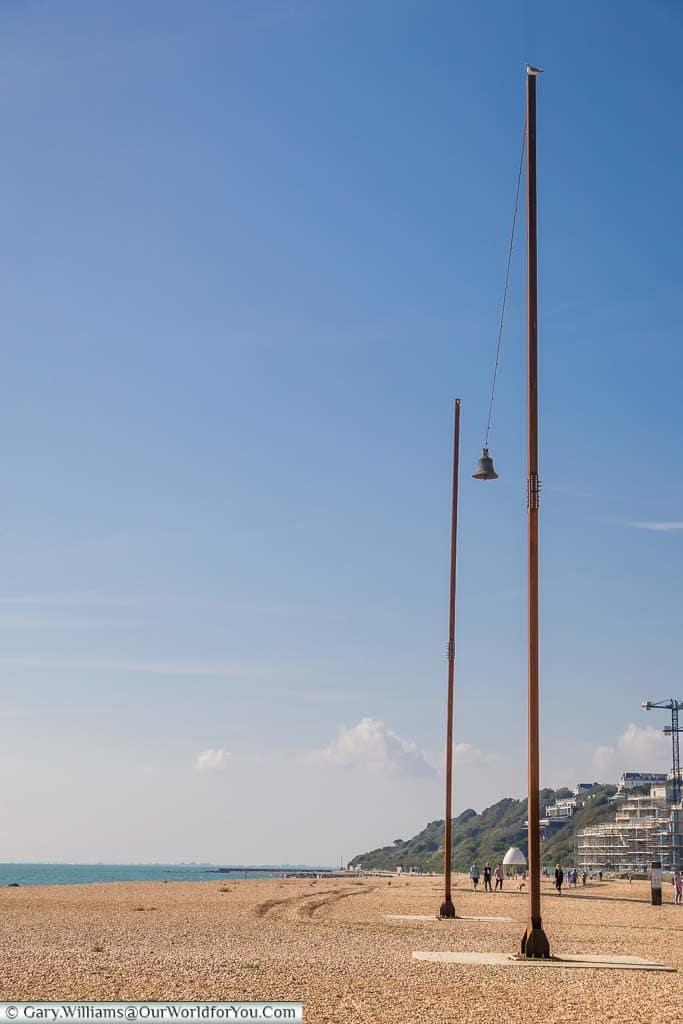 A single church bell suspended between two 2 20 metre steel pillars on Folkestone Beach as part of Creative Folkestone