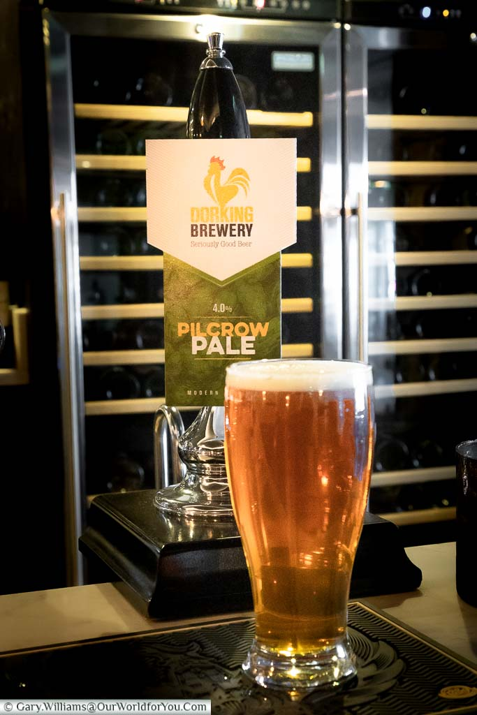 A pint of the Pilcrow Pale Ale in front of its pump in the Dozens bar in the White Horse Hotel, Dorking