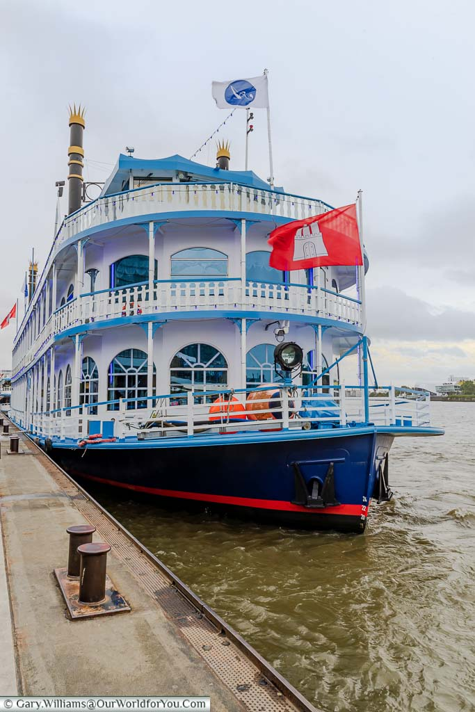 A paddle steamer pleasure boat flying the Hamburg flag featuring Hamburg Castle moored up at the landing stages of Hamburg.