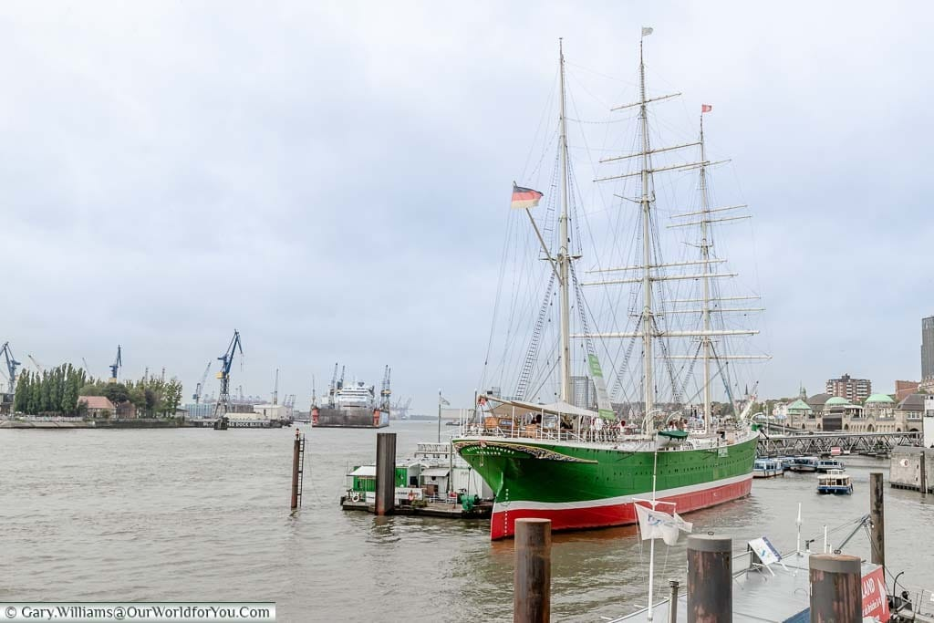 A tall ship with three masks and rigging flying the German flag moored up on the River Elbe. It now houses an escape room experience.