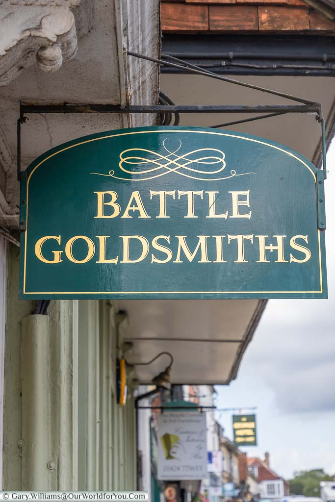 An ornate handpainted sign of gold on green for Battle Goldsmiths on Battle High Street, East Sussex