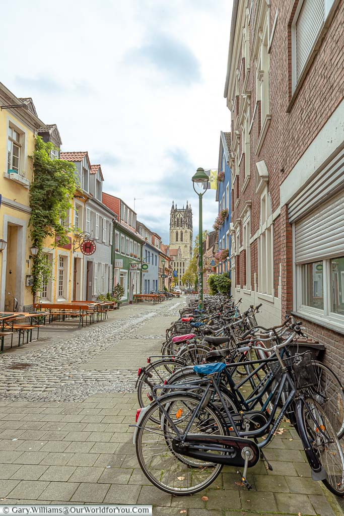 A series of bikes linned up in Kreuzstrasse, a colourful street full of traditional bars and houses all painted in bright colours. At the end of the lanes you can see the bell tower of the church Überwasserkirche.