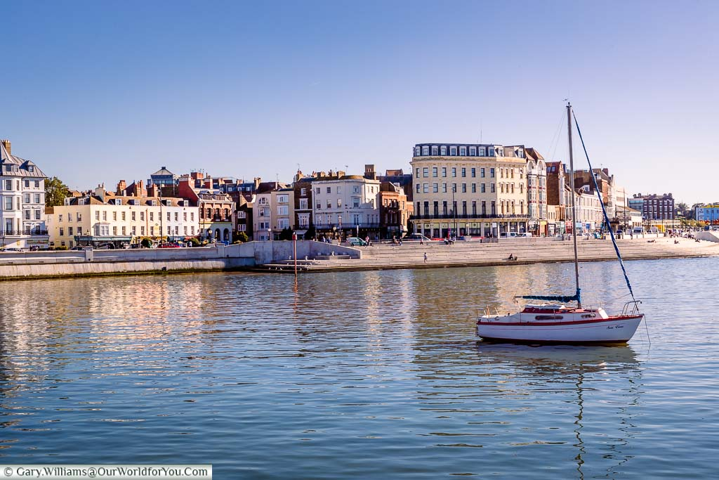 A lone small sailing boat anchored in Margate's harbour with a view overlooking the steps at the edge of The Parade