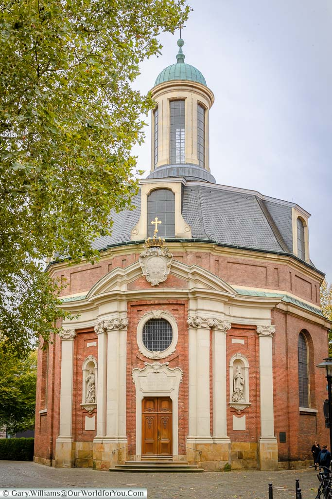 The red brick with cream trimmings Clemenskirche. The rood is grey tiled with a campanile style glass copper-domed bell tower.