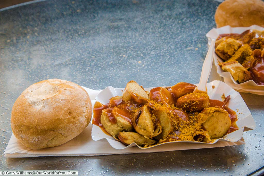 A couple of portions of Currywurst. Sliced sausages with lashings of curry sauce and dusted with curry powder, served with the obligatory crusty bread roll.