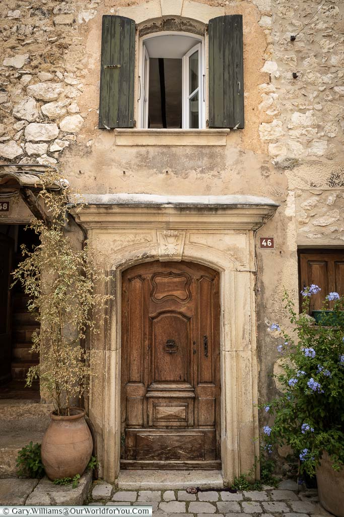 An ornate wooden door of number 46 set ain a stone building in Tourrettes sur Loup