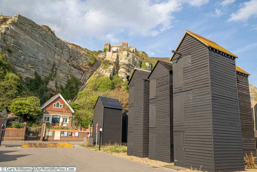 The view from Rock-a-Nore past the Wooden black weather-boarded net sheds to the East Hill funicular railway