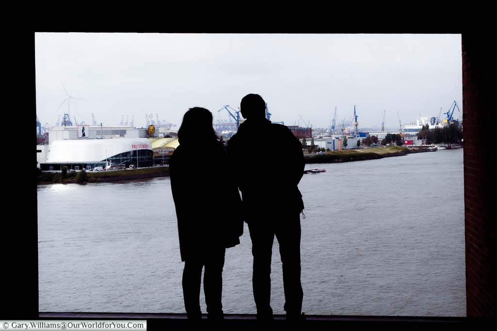 Silhouette of a couple looking through a window from the upper level of the Elbphilharmonie across the River Elbe.