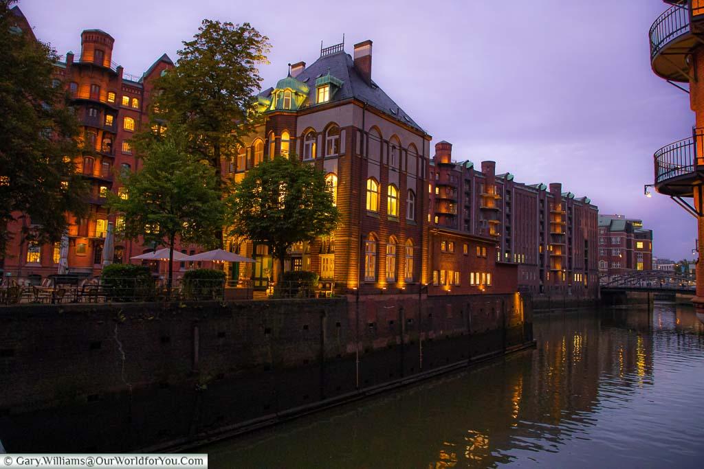 The Wasserschloß building in the Speicherstadt warehouse district of Hamburg at dusk.