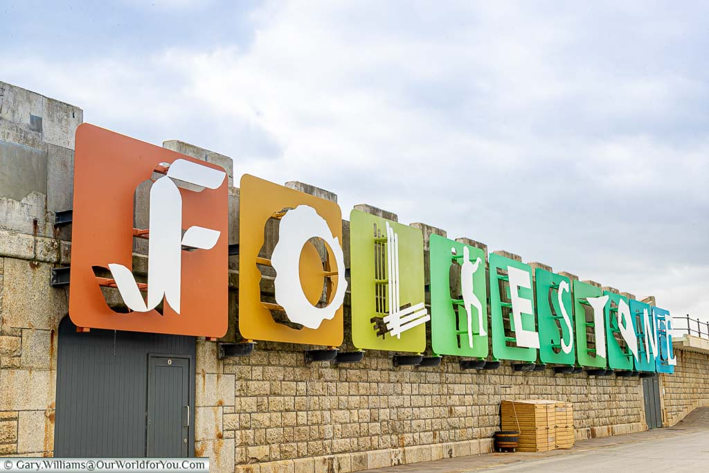 An art installation spelling out Folkestone on brightly coloured tiles on the wall of the harbour arm.