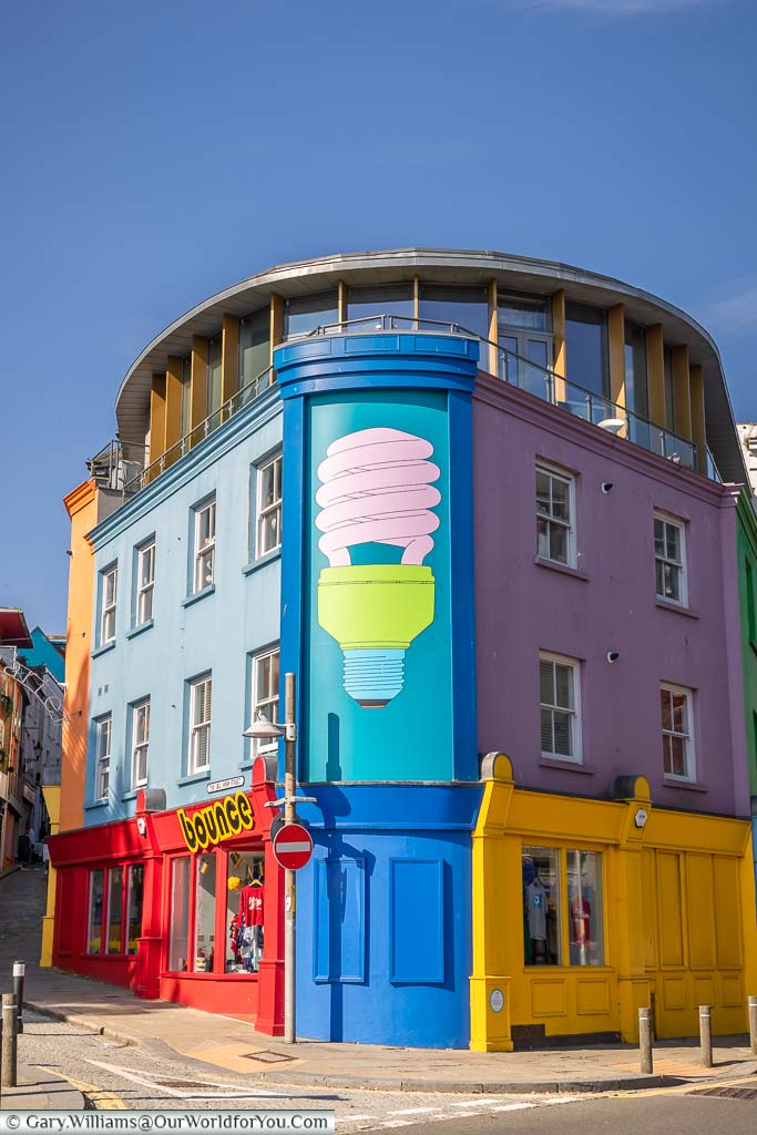 A mural of a brightly painted low energy light bulb painted on a building at the base of the Creative Corner end of the Old High Street in Folkestone