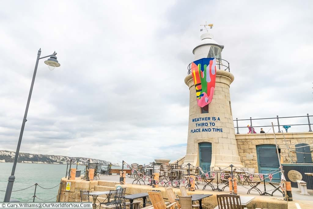 """Folkestone Lighthouse, now a bar with tables & chairs outside decorated with bunting. The lighthouse is also adorned with the Creative Artworks Folkestone flag and the inscription """"Weather is a third to Place and Time."""""""