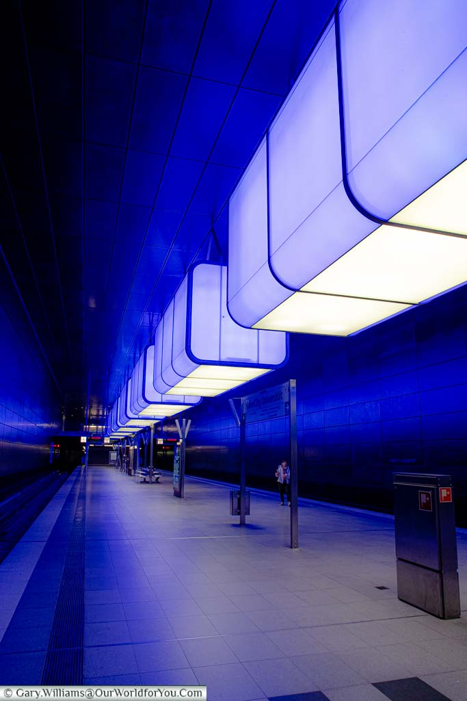 The modernist styled HafenCity Universität U-Bahn station in its blue phase where the overhead lighting is projecting a blue glow around the across the platform.