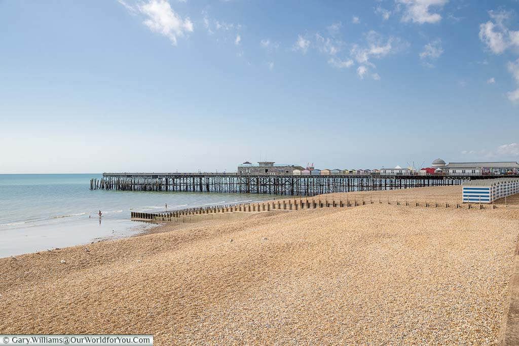 The view of Hastings pier from the promenade across the pebble beach