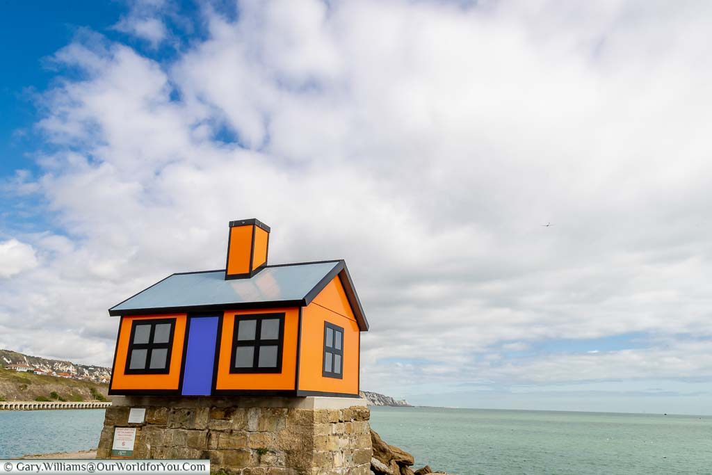 Holiday Home – By Richard Woods; An orange bungalow art installation with a purple door sitting on a plinth at the edge of the harbour car park overlooking the sea.