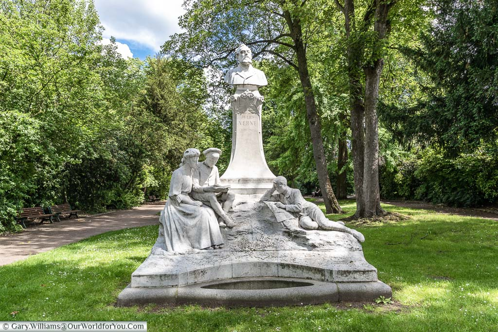 A monument to Jules Verne featuring his bust atop a plinth surrounded by a family reading his novels in Amien, Normandy