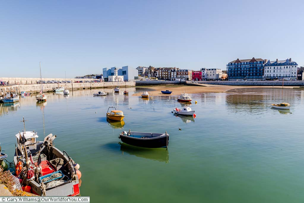 A collection of small boats anchored in Margate's harbour overlooking the Turner Contemporary Gallery