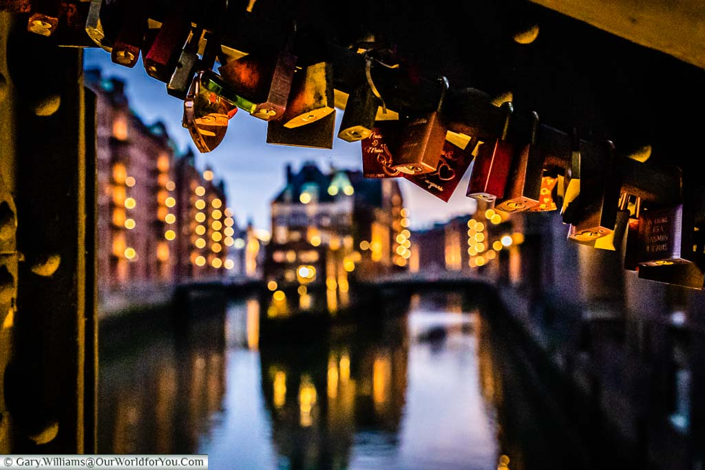 A view down the canals of Speicherstadt fro the Poggenmühlen-Brücke framed with love locks