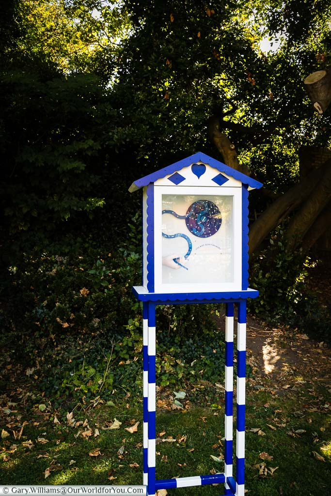 A blue and white wooden and glass box in the Bayle Pond which is part of the 'On the Track of St. Eanswythe's Waterway' art installation in Folkestone