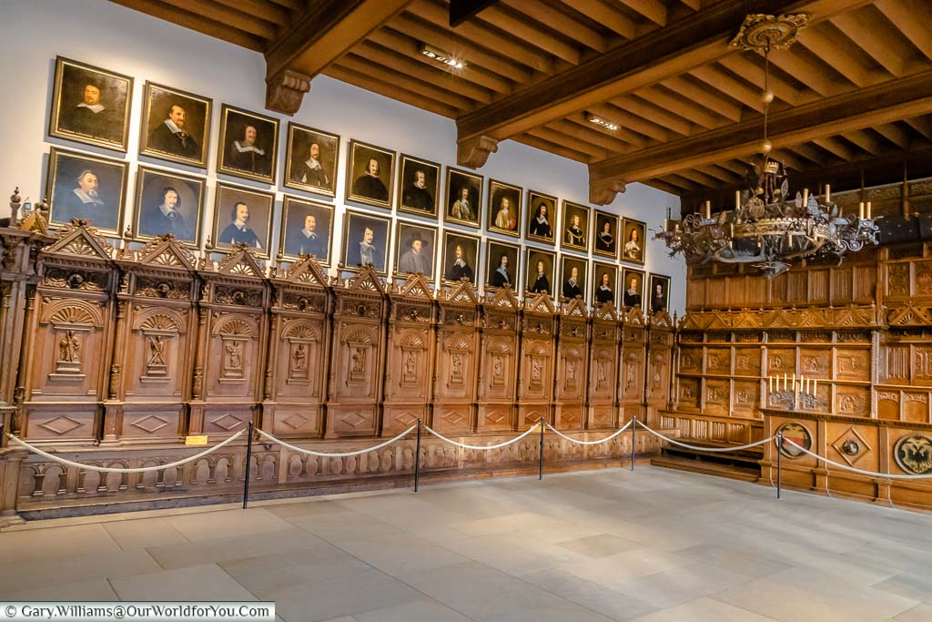 Inside the Hall of Peace. The original wood panelling survives, having been put into storage during World War 2. Along the far wall are 13 sections of intricately carved panels running up half the weight of the wall, with portraits above them of those involved in bringing peace.